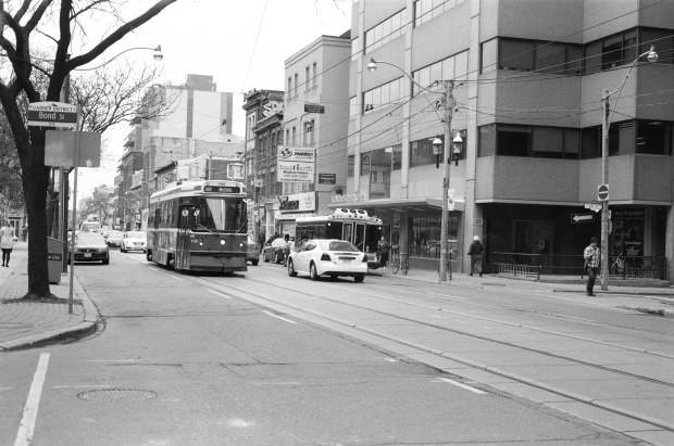 One of many TTC Streetcars rolling on the rails along Queen Street.