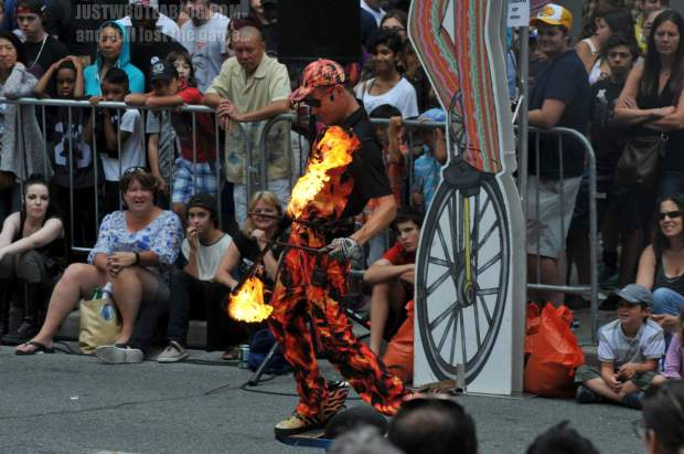 Fireguy playing with the devil sticks, one arm behind his back, while on his motorized one-wheel skateboard.